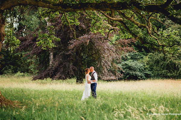 Happy couple kiss in the parkland at Homme House wedding venue in Herefordshire | CHWV