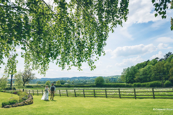 Happy couple taking a moment in the beautiful grounds at Hyde House and Barn wedding venue in Gloucestershire | CHWV
