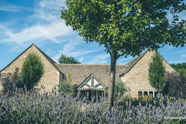 The barn and surrounding flowers at Hyde House and Barn wedding venue in Gloucestershire | CHWV