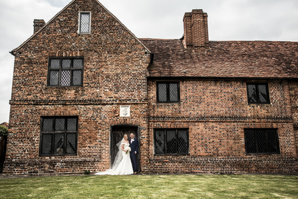 A happy couple outside the manor house at Lillibrooke Manor wedding venue in Berkshire | CHWV