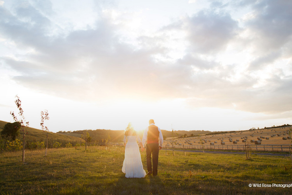 A happy couple in a field at Long Furlong Barn in West Sussex