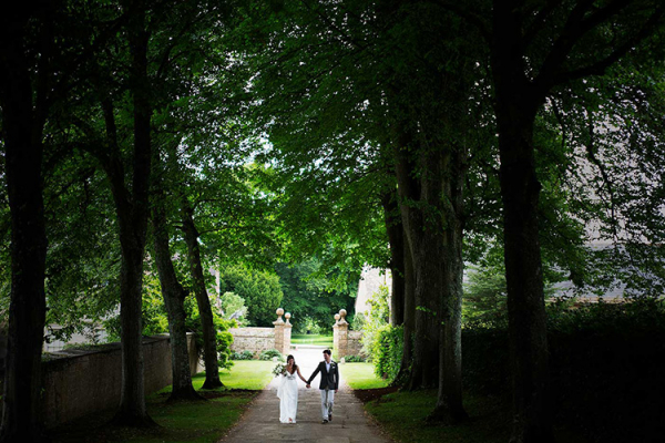 A happy couple walking down the Avenue at Mapperton wedding venue in Dorset | CHWV