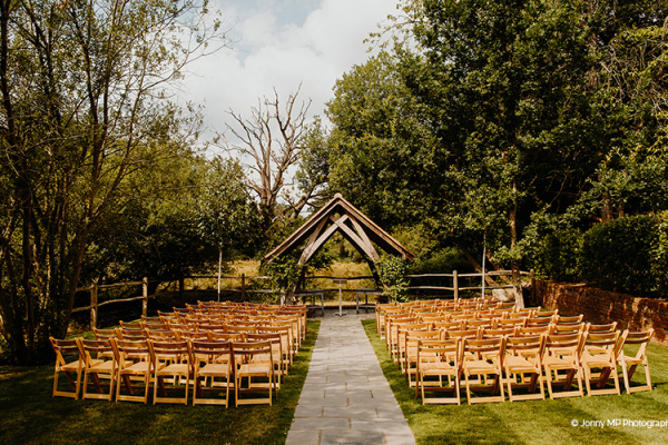 Set up for an outdoor ceremony under the arbor at Miillbridge Court wedding venue in Surrey | CHWV