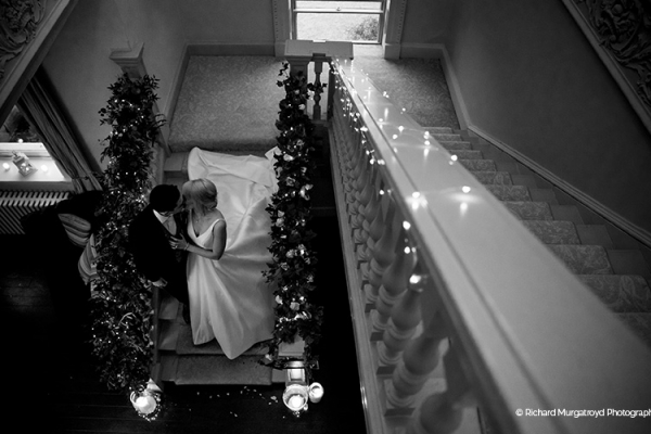A happy couple taking a moment on the staircase at Morden Hall country house wedding venue in London | CHWV