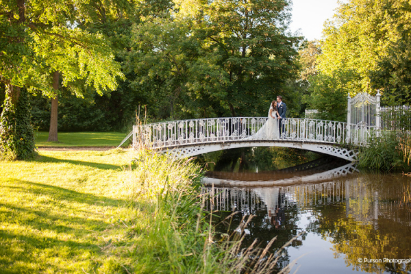 A happy couple taking a moment on the bridge at Morden Hall country house wedding venue in London | CHWV