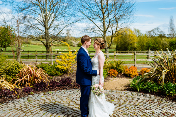 A bride and groom take a moment in the beautiful gardens at Mythe Barn wedding venue in Leicestershire | CHWV