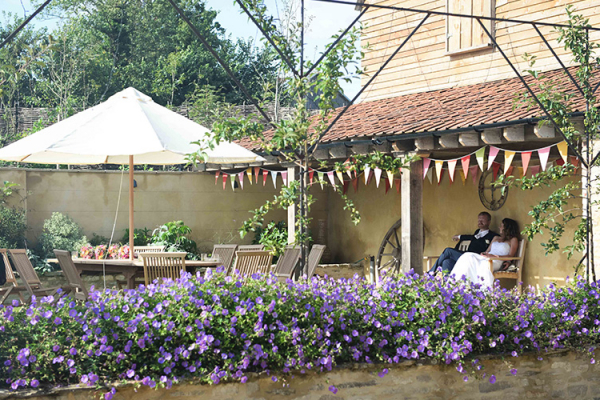 A couple relaxing in the courtyard at Oxleaze Barn wedding venue in Gloucestershire | CHWV