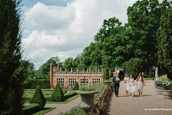 A bride and her bridesmaids walking to her wedding ceremony at Oxnead Hall wedding venue in Norfolk | CHWV