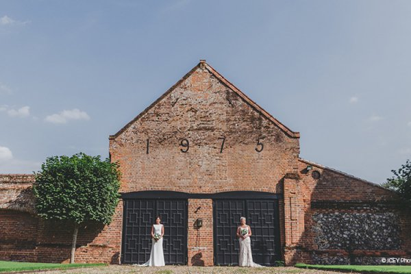A happy couple posing in the grounds at Oxnead Hall wedding venue in Norfolk | CHWV