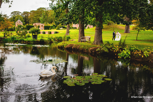 A happy couple taking a moment by the water gardens at Oxnead Hall wedding venue in Norfolk | CHWV