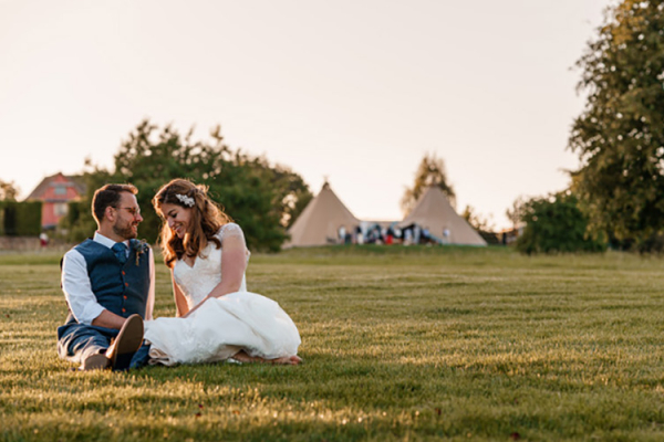 Couple sit on the grass at Pauntley Court country house wedding venue in Gloucestershire | CHWV