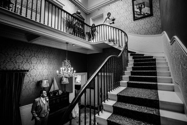 A bride making her way down the staircase at Penton Park wedding venue in Hampshire | CHWV