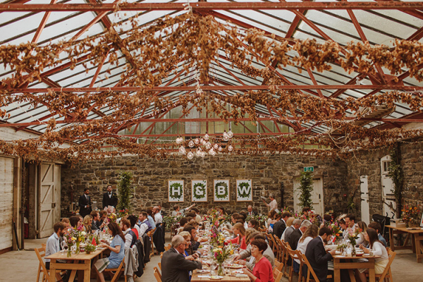 Guests sit down to a wedding breakfast in the Stables at Plas Dinam country house wedding venue in Carmarthenshire | CHWV