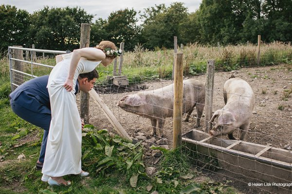 A happy couple taking a look at the pigs from River Cottage wedding venue in Devon | CHWV