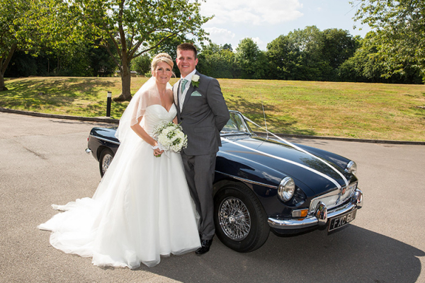 Happy couple posing by their wedding car at Robert Denholm House wedding venue in Surrey | CHWV