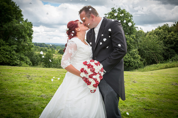 Confetti kiss in the beautiful grounds at Robert Denholm House wedding venue in Surrey | CHWV