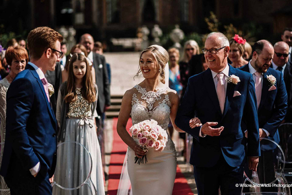 A radiant bride walking down the aisle at Rowton Castle wedding venue in Shropshire | CHWV