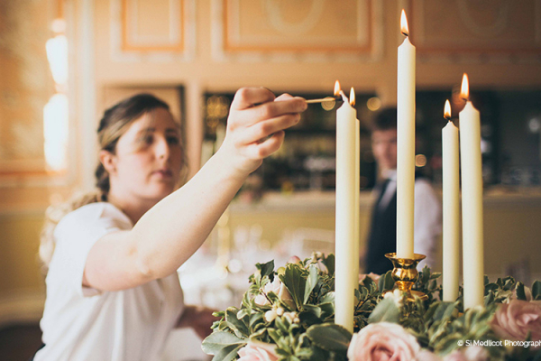 Lighting candles ready for a wedding breakfast at Rowton Castle wedding venue in Shropshire | CHWV