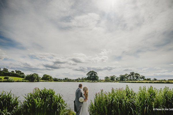 A happy couple viewing the lake at Sandhole Oak Barn