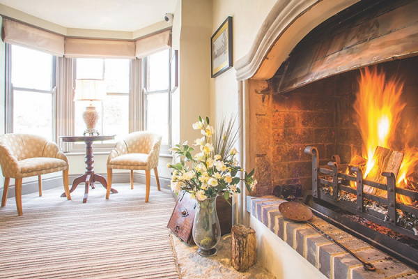 A roaring fireplace at Southdowns Manor wedding venue in West Sussex | CHWV