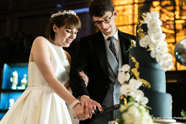 A happy couple cutting their cake at Stationers' Hall and Garden wedding venue in London | CHWV