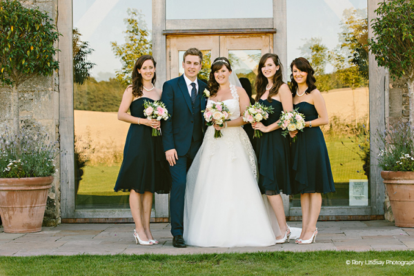 A bride and her bridesmaids outside at The Stone Barn wedding venue in Gloucestershire | CHWV