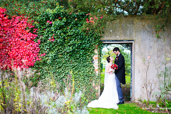 A happy couple in the beautiful grounds at Swynford Manor wedding venue in Cambridgeshire | CHWV