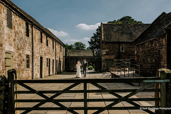 A happy couple in the courtyard at The Ashes barn wedding venue in Staffordshire | CHWV
