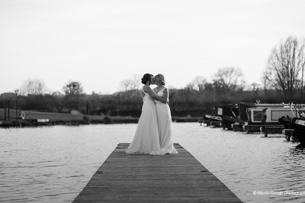A couple taking a moment on the jetty at The Boat House garden wedding venue in Staffordshire | CHWV