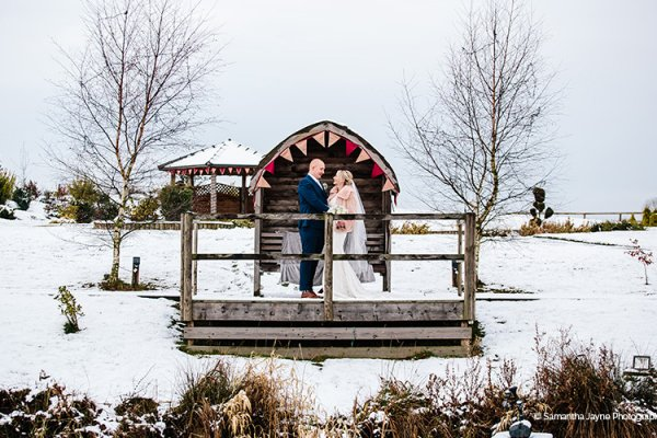 A happy couple posing in the snow at The Boat House garden wedding venue in Staffordshire | CHWV