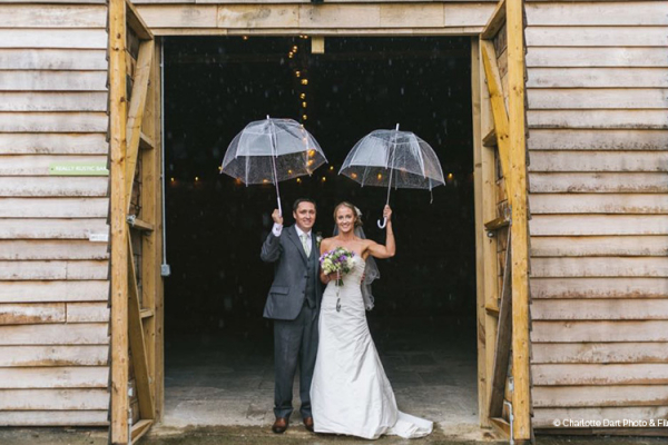 A happy couple with umberellas at The Green wedding venue in Cornwall | CHWV