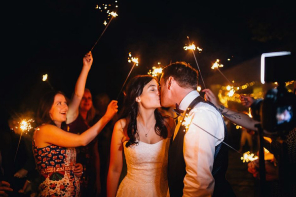 A happy couple celebrate with sparklers at The Green wedding venue in Cornwall | CHWV