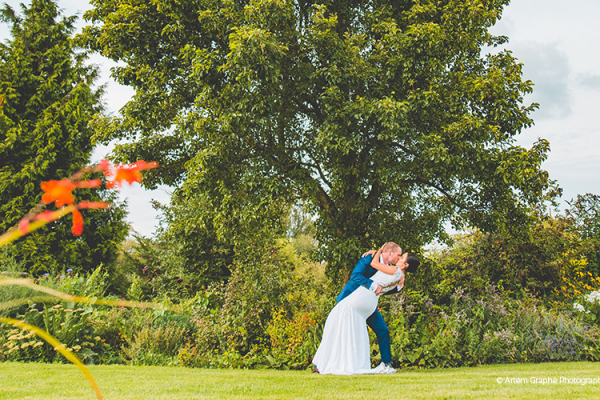 A couple taking a moment in the beautiful gardens at The Pear Tree wedding venue in Wiltshire | CHWV