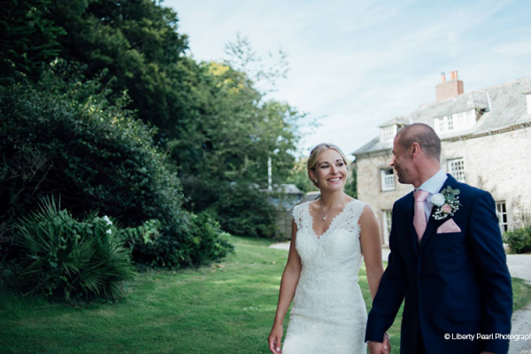 A happy couple enjoying the grounds at Tredudwell Manor wedding venue in Cornwall | CHWV
