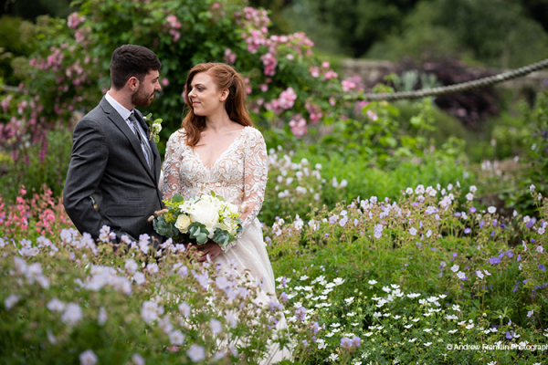 A happy couple take a moment in the beautiful gardens at Wakehurst wedding venue in West Sussex | CHWV