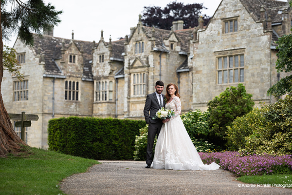 A happy couple in front of the house at Wakehurst wedding venue in West Sussex | CHWV