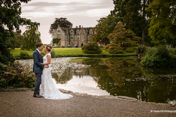 A happy couple in front of the lake at Wakehurst wedding venue in West Sussex | CHWV